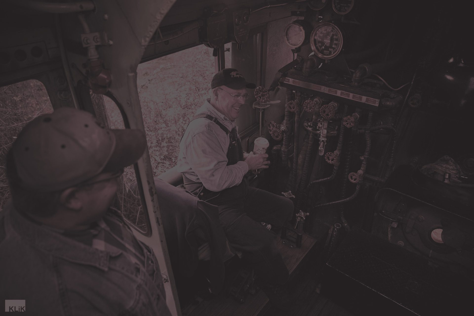 Conductor operating an antique locomotive - maroon overlay